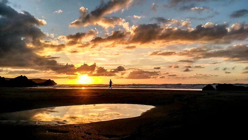 Persona andando por la playa con puesta del sol